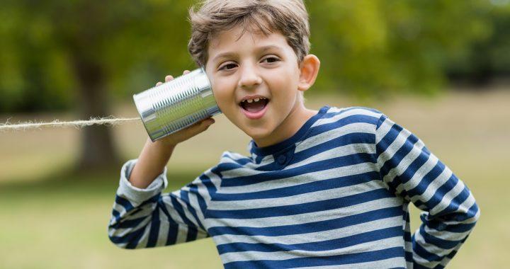Boy listening through tin can phone